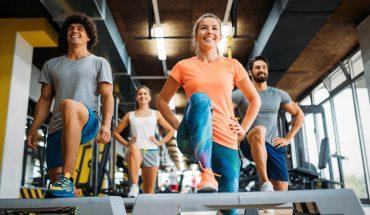 Zadowolone osoby ćwiczące rozciąganie napodestach